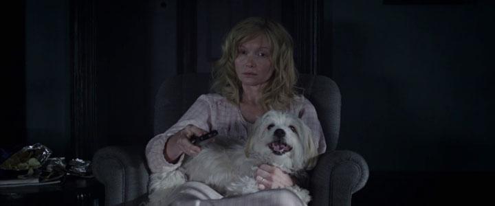 Amélia assistindo TV com o cachorro no colo no filme Babadook